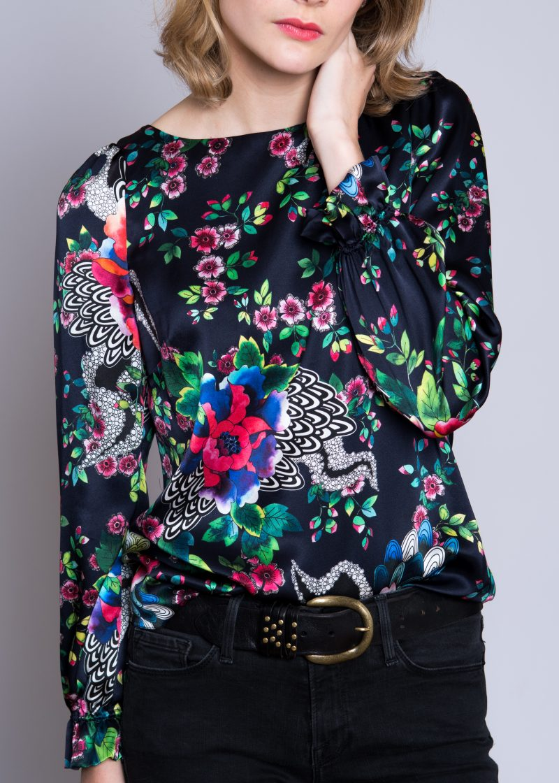 close up of model, silk blouse, navy background with floral print