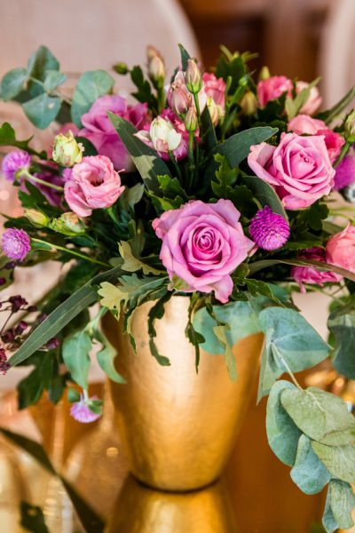 pink roses and foliage in gold vase